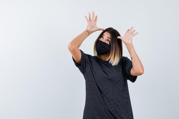Giovane donna che tiene le mani sulle tempie, guardando sopra in abito nero, maschera nera e guardando divertito, vista frontale.