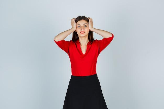 Giovane donna che tiene le mani sulle tempie in camicetta rossa