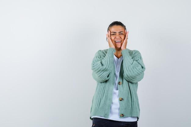 白いシャツとミントグリーンのカーディガンで顔に手をつないで幸せそうに見える若い女性