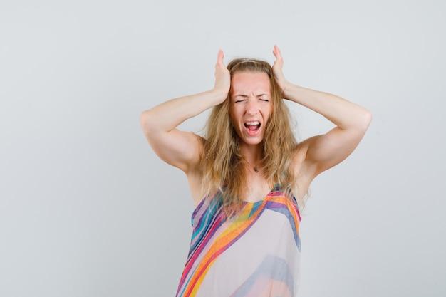 若い女性の夏のドレスで頭に手を繋いでいるとイライラして