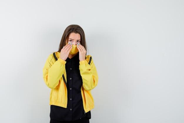 Молодая женщина, взявшись за руки под глазами и выглядя испуганной