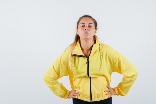 Young woman holding hands on waist while pouting lips in yellow raincoat front view.