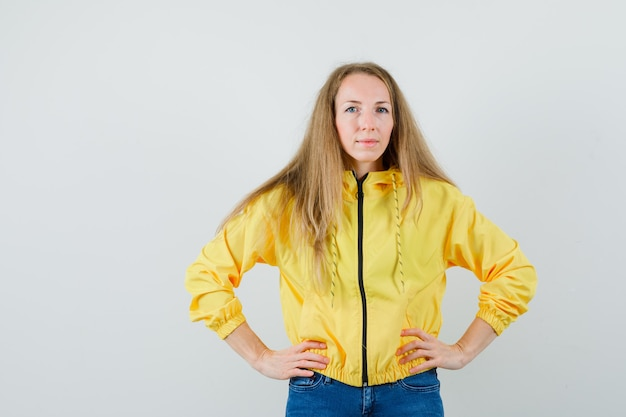 Young woman holding hands on waist in yellow bomber jacket and blue jean and looking attractive , front view.