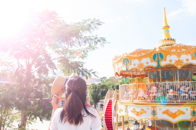 Young woman holding hat in sunny day with amusement park ride background