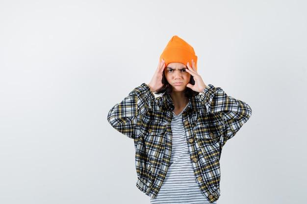 痛みを伴うオレンジ色の帽子の市松模様のシャツで指で頭を保持している若い女性