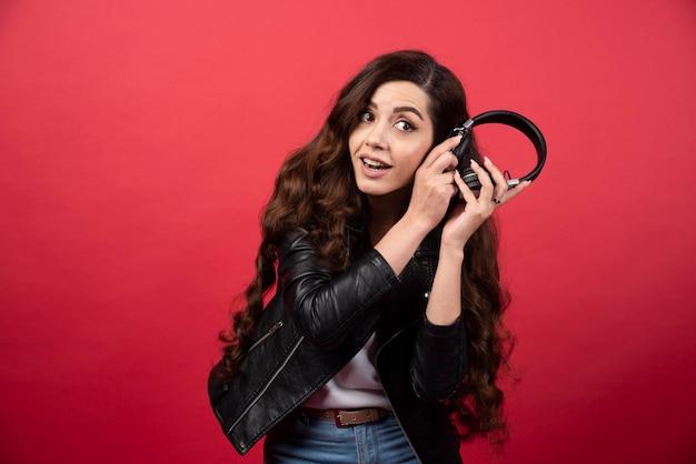 ヘッドフォンを持ち、赤い背景にポーズをとっている若い女性。高品質の写真