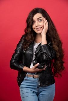 Молодая женщина держит наушники и позирует на красном фоне. фото высокого качества