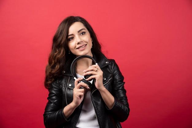 Giovane donna che tiene le cuffie e posa su uno sfondo rosso. foto di alta qualità