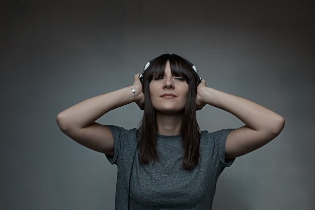 Young woman holding headphones with closed eyes