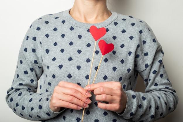 밝은 배경에 막대기에 하트를 들고 젊은 여자. 발렌타인 데이, 생일. 배너.