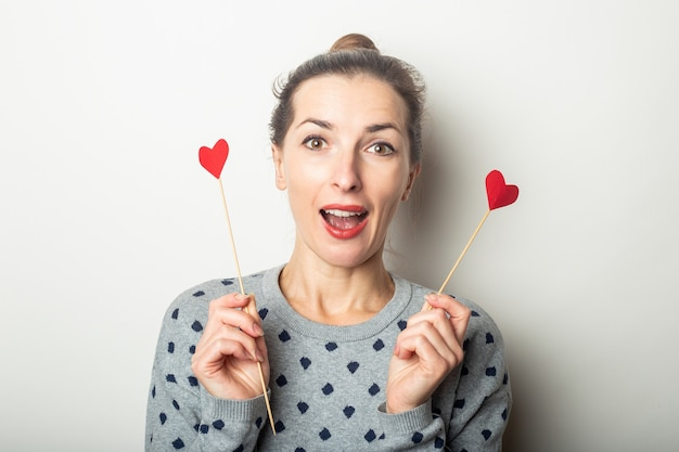Young woman holding hearts on sticks on a light background. valentine's day, birthday. banner. Premium Photo