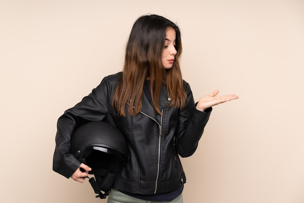 Young woman holding a helmet over isolated wall