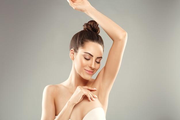 Молодая женщина держит руки вверх и показывает чистые подмышки