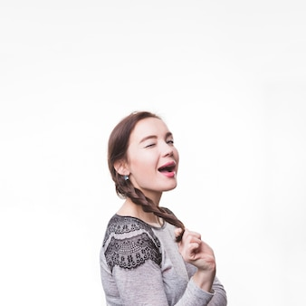 Young woman holding her braid blinking on white background
