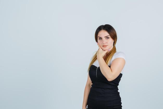 Giovane donna che si tiene il mento con la mano