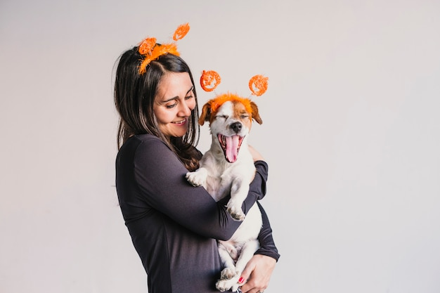 Young woman holding her cute small dog over white background. matching pumpkin diadems. halloween concept