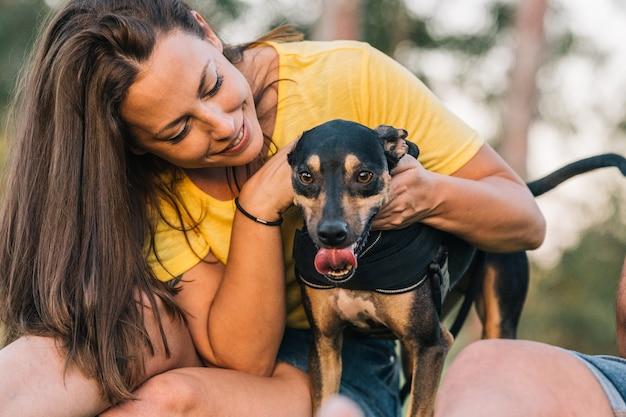 草の上に座っている頭で彼女の犬を保持している若い女性。公園で彼女の犬と美しい女性