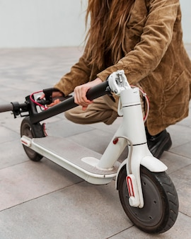 Young woman holding her electric scooter