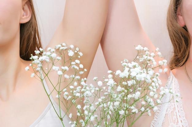 手を上げてカスミソウを手に脇の下を見せている若い女性は、透明な肌を滑らかにします。女の子はきれいな脇の下を見せます。美しさの肖像画。脱毛と脱毛。
