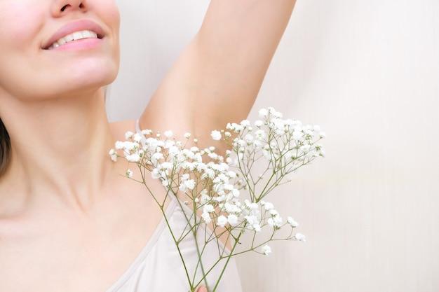 Молодая женщина держит руки вверх и показывает подмышки с гипсофилой в руке, гладкая прозрачная кожа подмышек