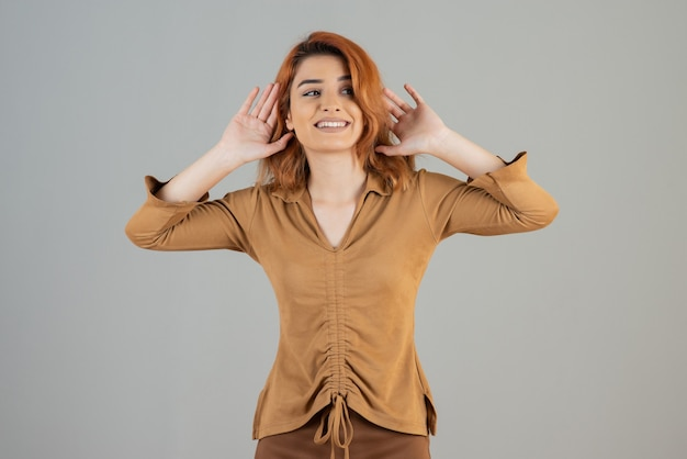 Молодая женщина держит руки вверх и улыбается на серой стене Premium Фотографии