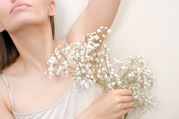 Young woman holding her hands up and showing armpits with gypsophila in her hand, armpits smooth transparent skin. the girl shows a clean armpit. beauty portrait. hair removal and depilation.