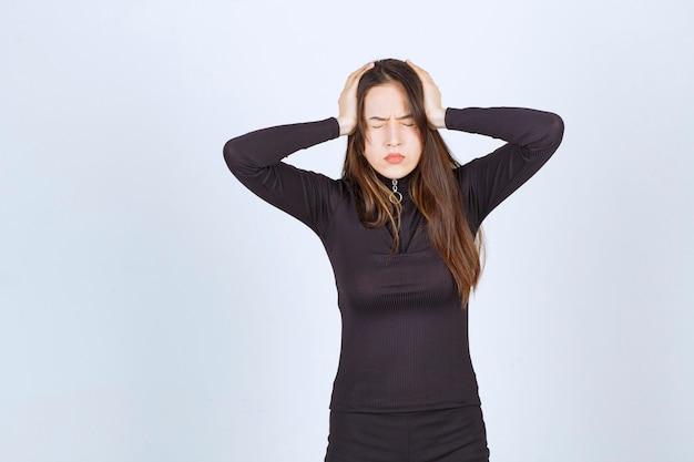 Giovane donna che tiene la testa perché ha mal di testa o si è emozionata