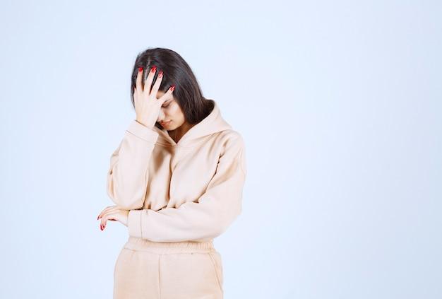 Молодая женщина держит ее за голову, когда у нее болит голова