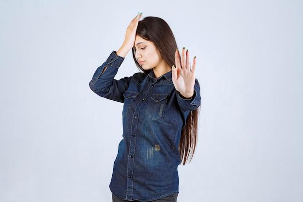 倦怠感や頭痛で頭を抱えている若い女性
