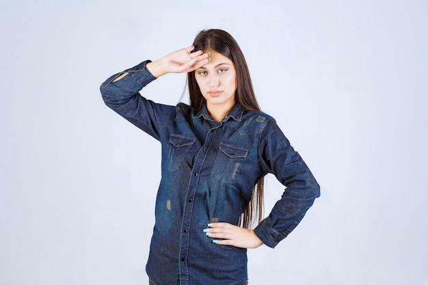 Молодая женщина, держащая ее за голову, когда она устала или у нее болит голова