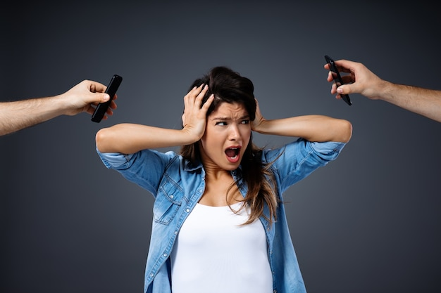 Young woman holding her head and screaming because she have to answers phone call.