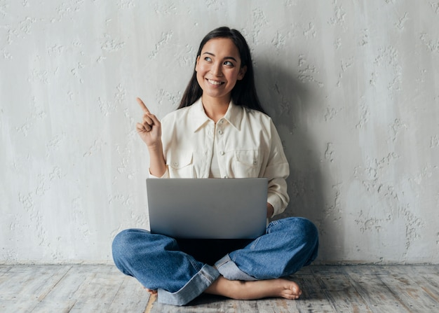 Young woman holding her laptop and looking up