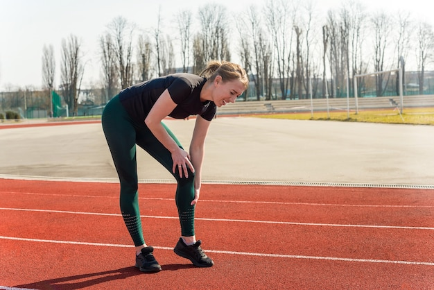 경기장에서 고통에 그녀의 다리를 들고 젊은 여자. 탈구 된 관절의 달리기 스포츠 부상 골절.