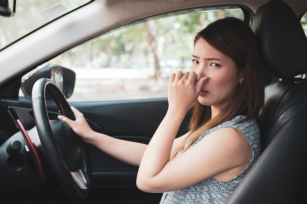 Young woman holding her nose because of bad smell in car