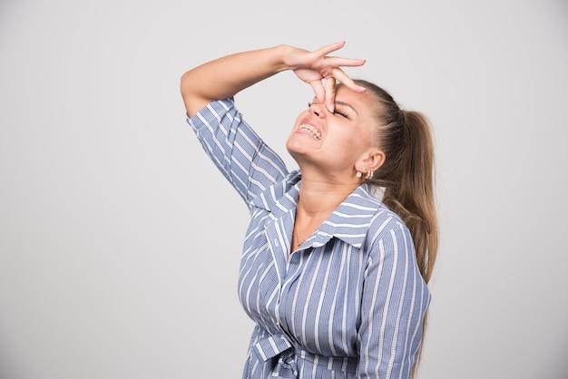 Giovane donna che tiene il naso sul muro grigio.