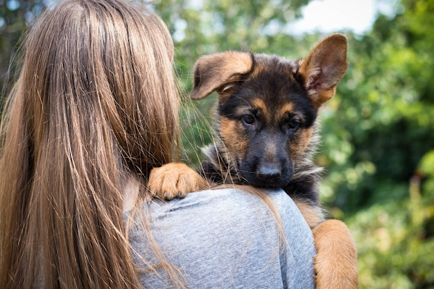 Young woman holding her puppy on shoulder