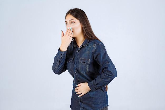Giovane donna che tiene il suo stomaco mentre è incinta e vomita