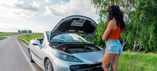頭を抱えた若い女性がボンネットを開けた側面の壊れた車道路でボンネットを上げて損傷したエンジンを見る