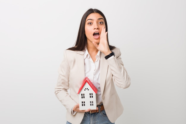 Young woman holding a house icon shouting excited to front.