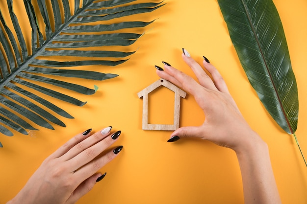 オレンジ色の背景に手で家を保持している若い女性
