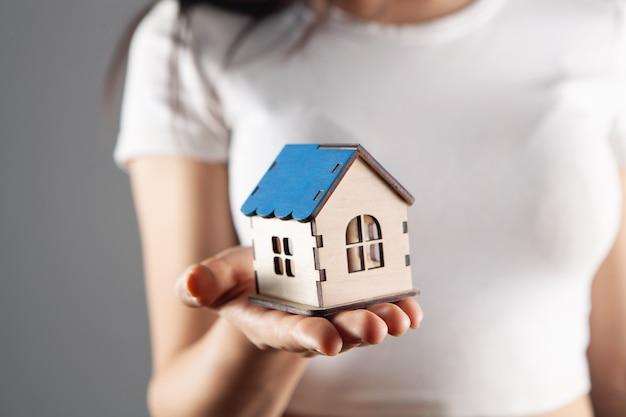 手に家を保持している若い女性