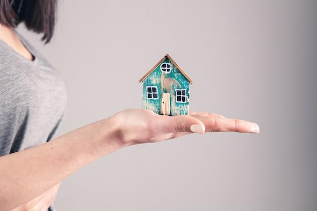 灰色の家を持つ若い女性