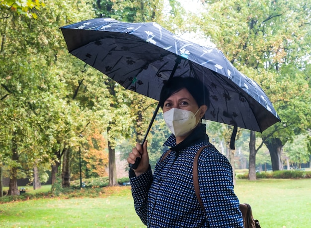 Young woman holding humbrella in a park during rainy day urban and nature lifestyle