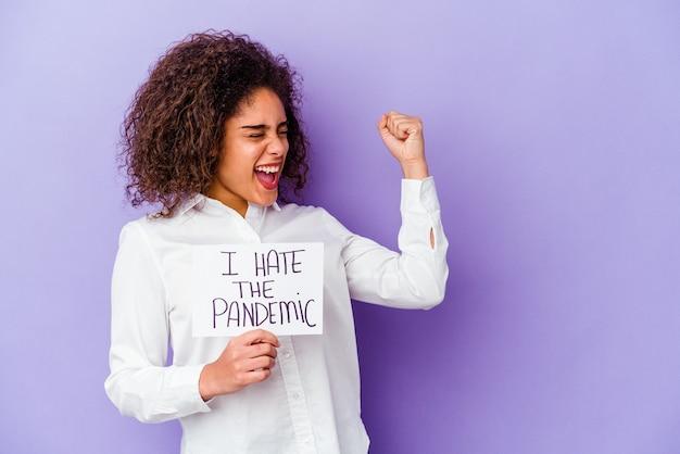 나는 승리, 승자 개념 후 주먹을 올리는 보라색 벽에 고립 된 유행성 현수막을 싫어하는 젊은 여자