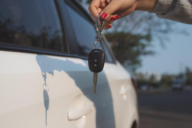 手車のキーを保持している若い女性。