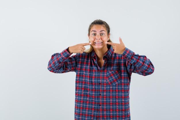 Молодая женщина держит указательные пальцы возле рта, заставляет улыбаться в клетчатой рубашке и выглядит счастливой