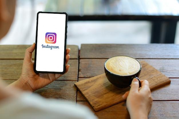 스마트 폰 디스플레이에 instagram 응용 프로그램을 보여주는 아이폰 스마트 폰을 들고 젊은 여자