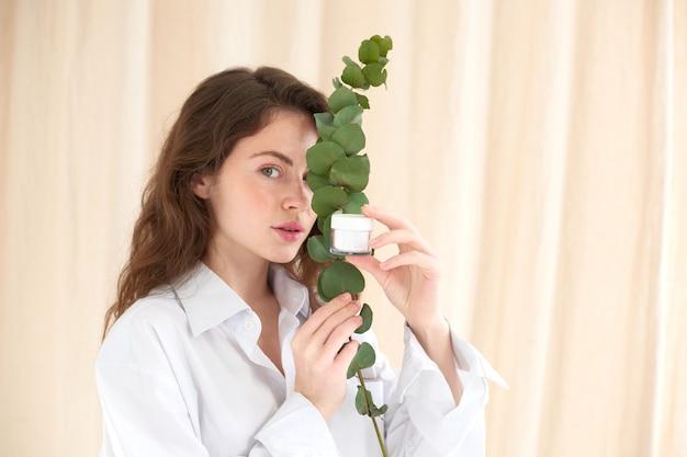 Молодая женщина, держащая банку со сливками и веточку растения, скрывает глаз