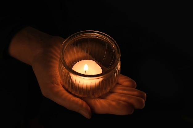 Young woman holding jar with burning candle in darkness
