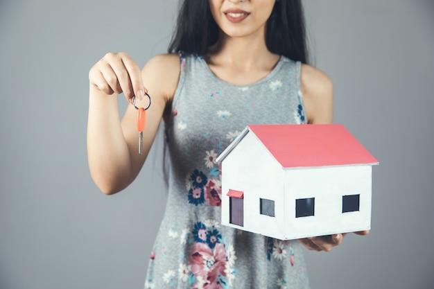Молодая женщина, держащая ключ и модель дома